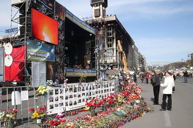 Цветы и свечи у портретов погибших во время февральских беспорядков на площади Независимости в Киеве
