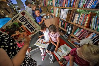 Школьники читают книги в автобусе передвижной библиотеки во дворе школы на хуторе Клетском Волгоградской области.