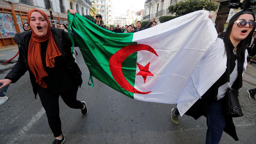 Студенты с национальным флагом во время протестной акции в Алжире, 5 марта 2019 года