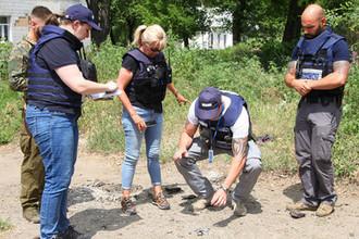 Сотрудники Организации по безопасности и сотрудничеству в Европе (ОБСЕ) собирают осколки снарядов недалеко от здания городской детской клинической больницы №4 в Донецке, 19 июня 2019 год