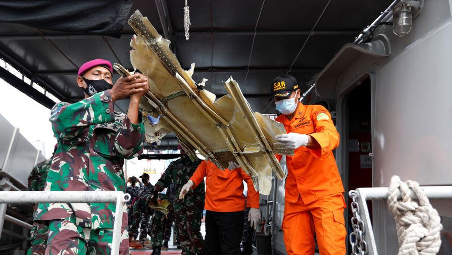 Сотрудники индонезийского ВМФ и спасатели с обломками самолета Boeing 737-500 авиакомпании Sriwijaya Air в порту Танджунг-Приок в Джакарте, 10 января 2021 года