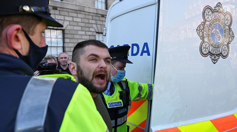 Полицейские задерживают мужчину в День Святого Патрика в Дублине, 17 марта 2021 года