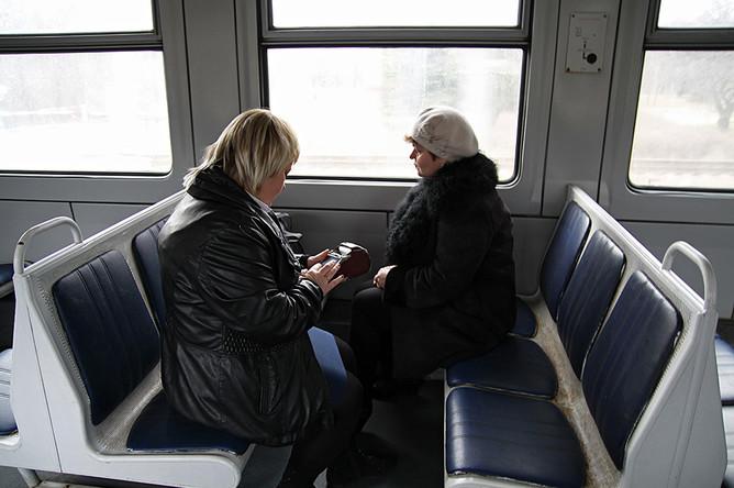 Кондуктор проверяет билеты у пассажира первого электропоезда, следующего в город Луганск со станции Ясиноватая в Донецкой народной республике