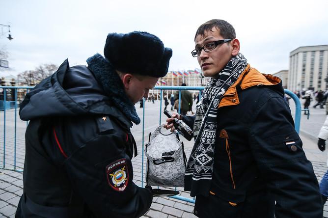 Сотрудник полиции проводит досмотр личных вещей прохожего на Манежной площади
