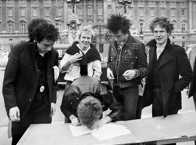 Группа Sex Pistols и их менеджер Малкольм Макларен (справа) подписывают договор со звукозаписывающей компанией у Букингемского дворца в Лондоне, 1977 год