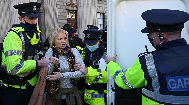 Полицейские задерживают женщину в День Святого Патрика в Дублине, 17 марта 2021 года