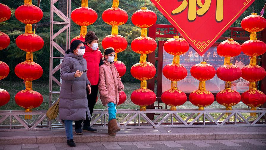 Люди фотографируются на фоне отмененной храмовой ярмарки в Пекине, Китай, 25 января 2020 года
