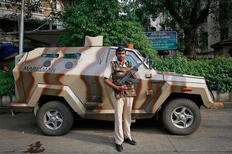 Сотрудник спецподразделения полиции Индии около бронированного автомобиля