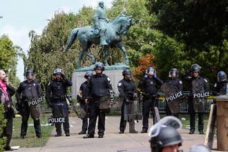 Полиция около памятника генералу армии конфедератов Роберту Ли во время демонстрации националистов в Шарлотсвилле, штат Вирджиния, 12 августа 2017 года