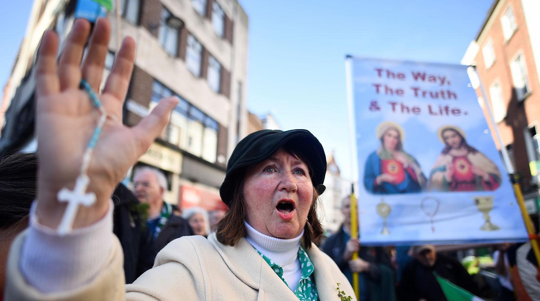 Женщина во время праздничного шествия в День Святого Патрика в Дублине, 17 марта 2021 года