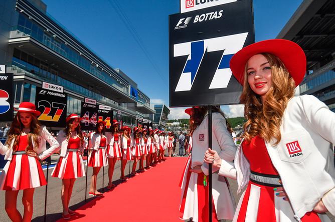 Девушки держат таблички с номерами мест гонщиков на трассе перед гонкой на российском этапе чемпионата мира по кольцевым автогонкам в классе «Формула-1»
