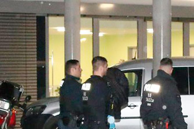 Полиция выводит преступника из здания Schlosspark-Klinik