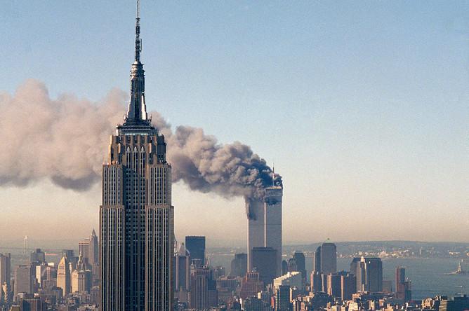 Башни-близнецы Всемирного торгового центра горят за зданием Эмпайр-стейт-билдинг после теракта 11 сентября 2001 года