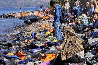 Сотни беженцев из Турции прибывают на лодках на пляж греческого острова Лесбос после пересечения Эгейского моря