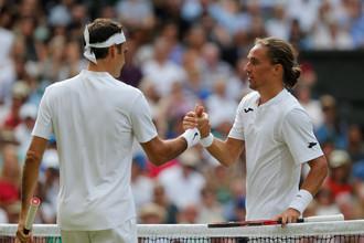 Украинский теннисист Александр Долгополов пожимает руку Роджеру Федереру после того, как неожиданно сообщил о том, что не может продолжить поединок
