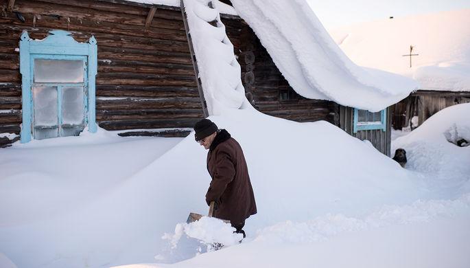 Мужчина расчищает дорожку от снега в деревне Бобровка, 25 января 2017 года
