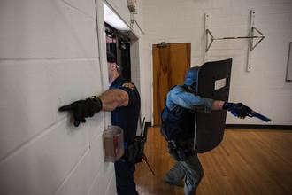 Офицеры военной полиции корпуса морской пехоты США штурмуют школу во время учений