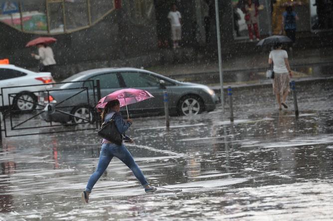 Люди на улице у метро «Партизанская» во время сильного дождя в Москве