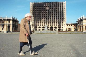 Абхазия. Сухуми. На снимке: пожилая женщина идет мимо сгоревшего Дома правительства, 1993 год