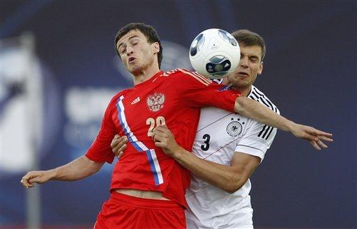 Полузащитник молодежной сборной России Шота Бибилов не пускает к мячу защитника команды Германии Стефана Тескера