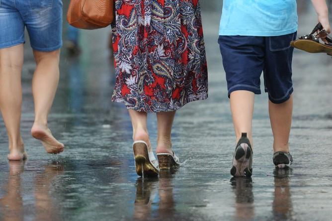 Прохожие идут по улице во время сильного дождя в Москве