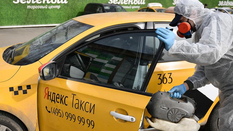 Сотрудник компании во время дезинфекционной обработки автомобилей такси