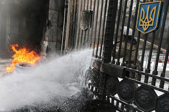 Пожарный тушит горящие автомобильные покрышки, которые подожгли участники акции протеста бойцов батальона «Айдар» и их сторонники у здания министерства обороны Украины в Киеве
