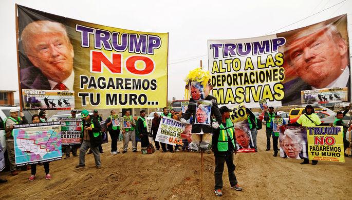 Плакаты «Трамп, мы не будем платить за стену» и «Трамп, останови массовые...