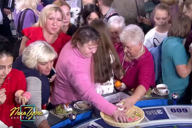 Зрители программы «Поле чудес» забирают еду с игрового барабана в конце передачи, февраль 2019 года