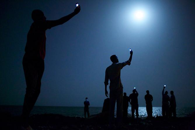 Фотограф Джон Стенмейер из США, работающий для агентства VII, снял по заказу National Geographic африканских мигрантов на побережье Джибути, пытающихся поймать слабый сотовый сигнал из Сомали. Снято в феврале 2013 года